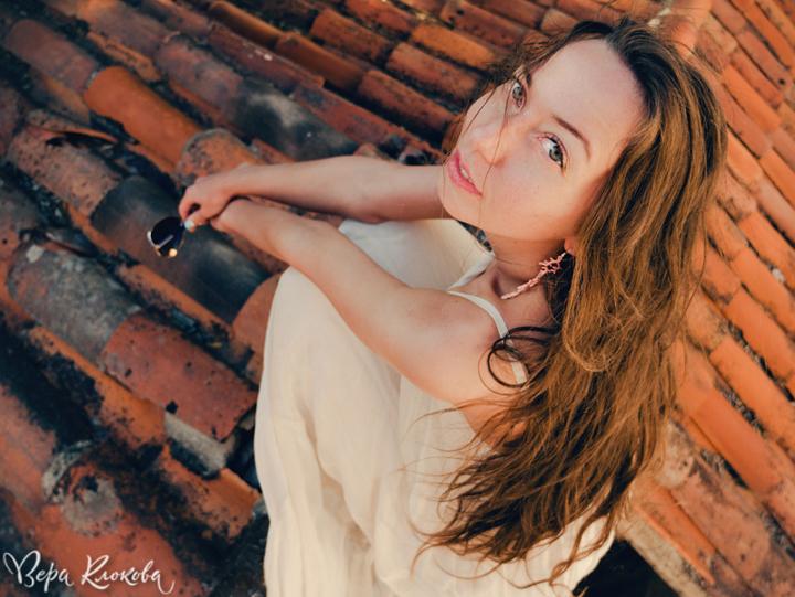 близкий портрет девушки на фоне черепичных крыш