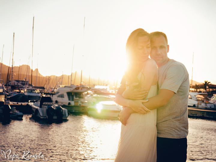 романтический портрет влюбленной пары в лучах закатного солнца на фоне моря