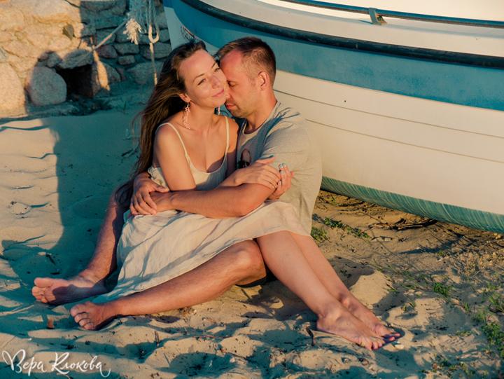 мечтательный портрет на закатном пляже на фоне бело-голубых лодок